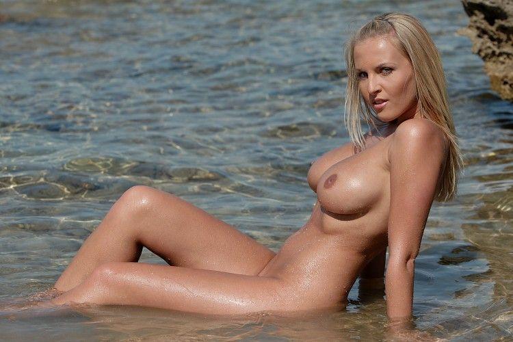 Молодая пышногрудая блондинка на пляже