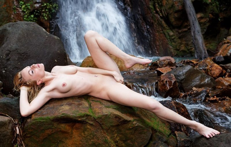 young blonde girl in front of the waterfall