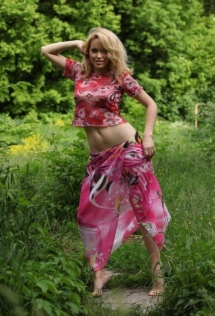 young blonde girl reveals in the nature on the forest glade