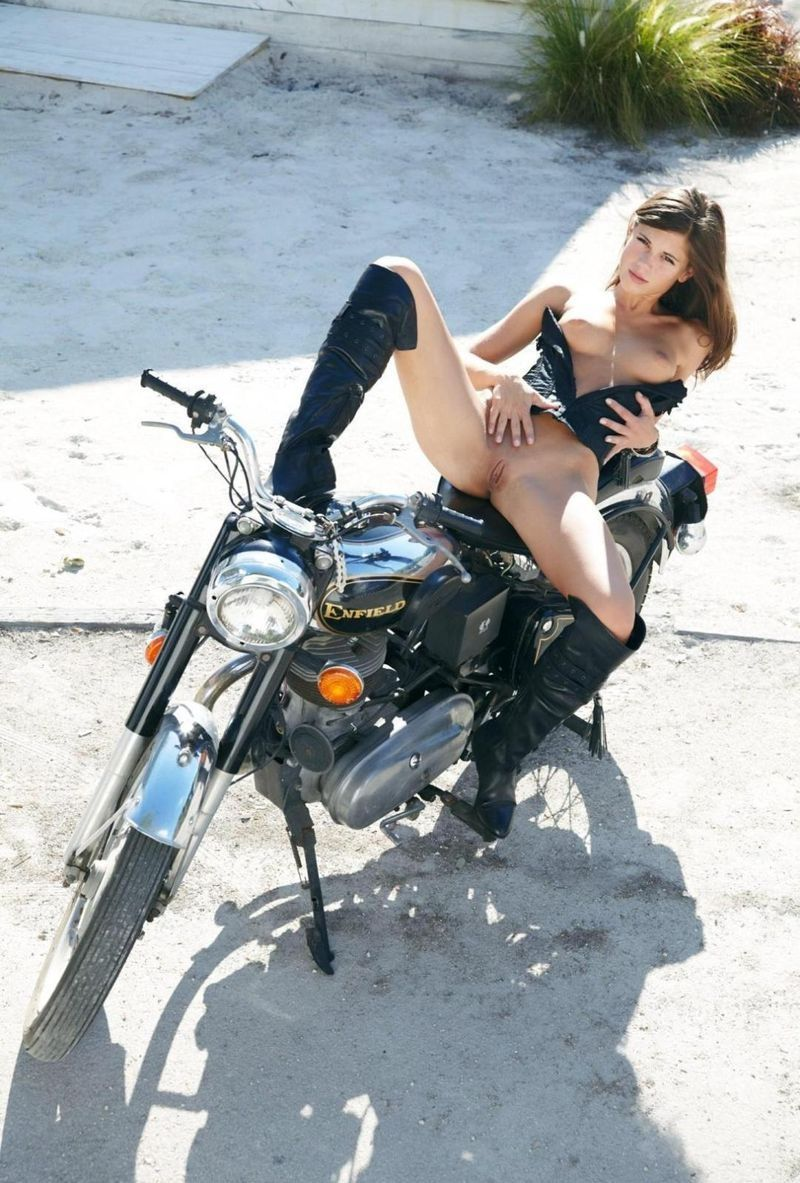 young brunette girl with a black corset and boots posing on a motorcycle