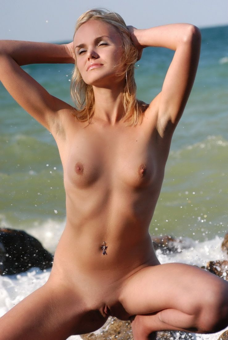 young blonde girl gets undressed from jeans on the rocky beach