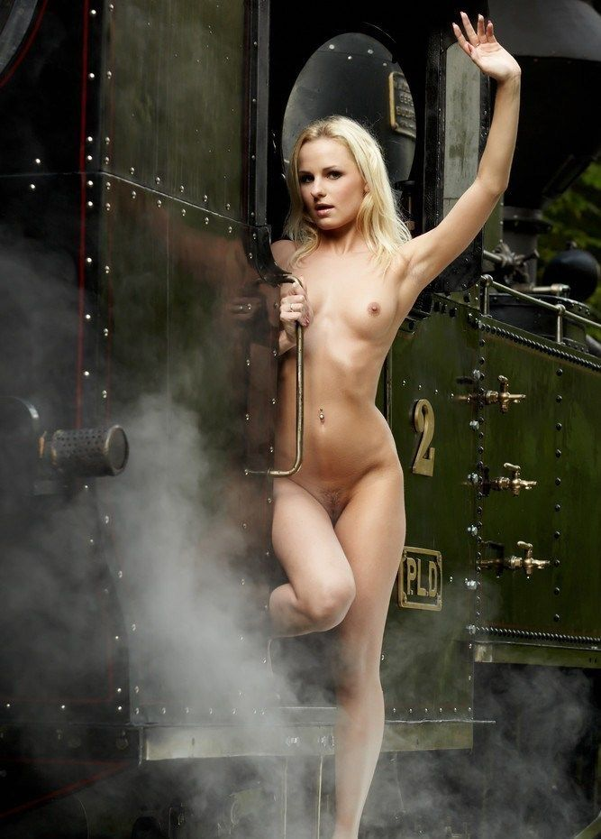 young blonde girl outside with the old steam locomotive