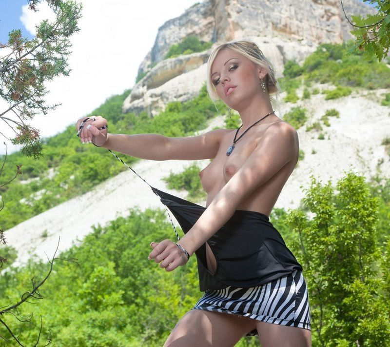 young blonde girl undresses herself at the mountain