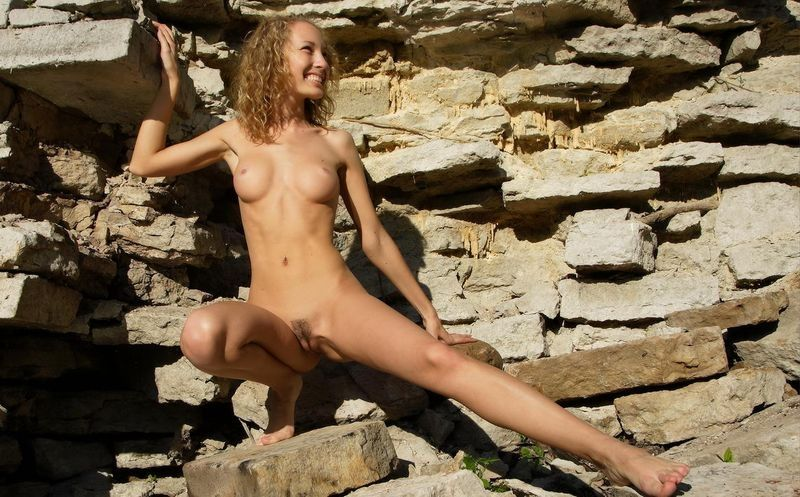 cute young curly blonde girl outside at the wall of rocks