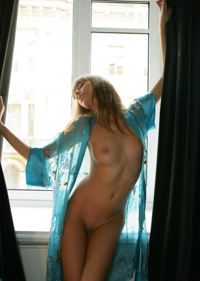 young brunette girl wearing blue nightgown in the bedroom