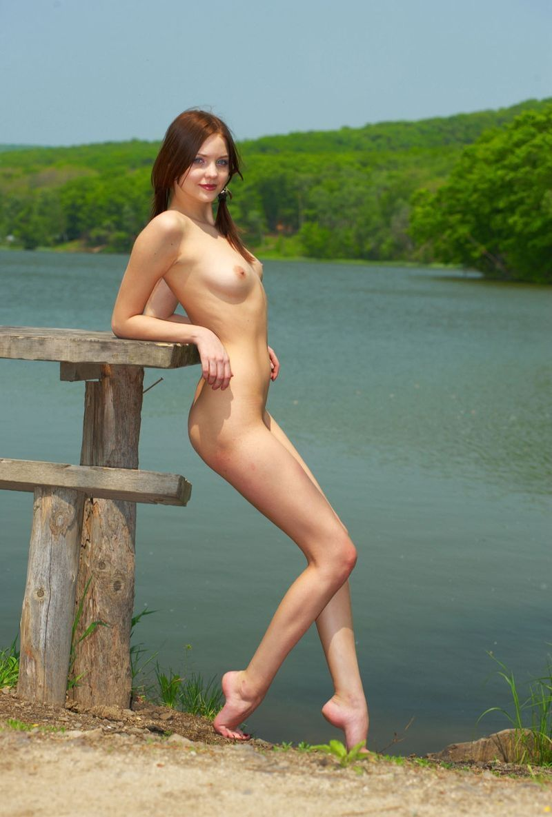 young brunette girl outside by the lake