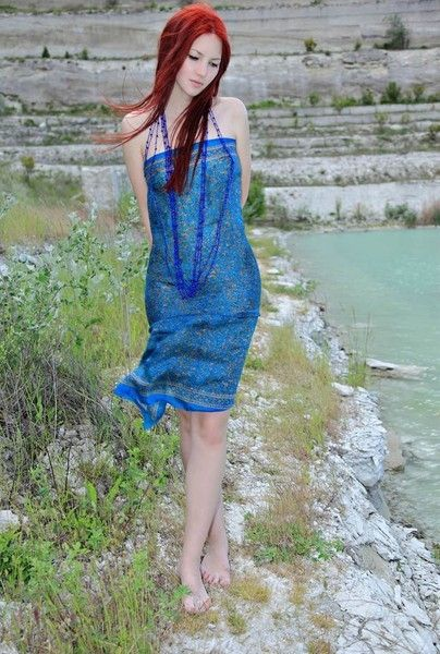 young red haired girl by the lake with blue necklace