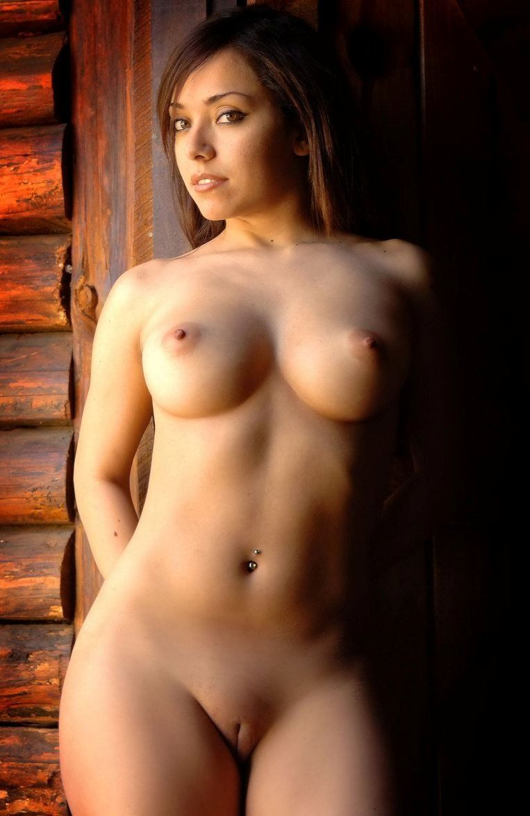 young brunette girl with a navel piercing undresses her sweater in the wooden barn