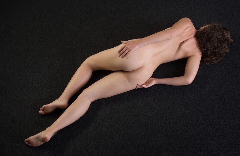 young curly brunette girl shows off on the floor in the studio