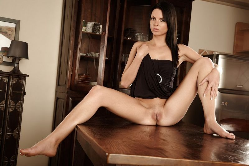 young brunette girl reveals on the table in the kitchen