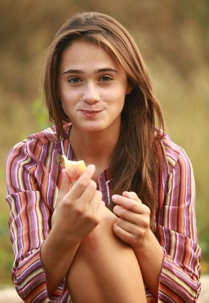 cute young brunette girl reveals outside in the nature on logged tree trunks
