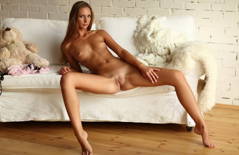 cute young blonde girl with a teddy bear undresses her pink brassiere and knickers on the white couch