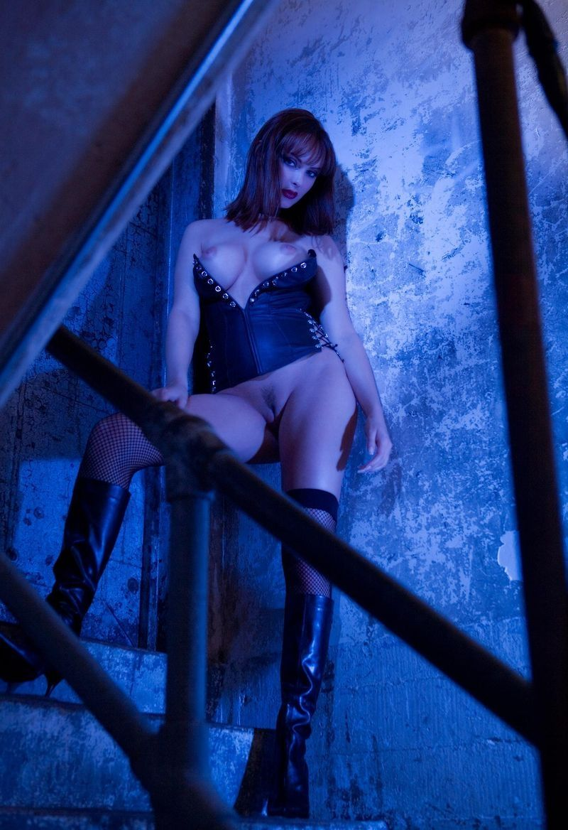 brunette girl wearing erotic outfit on the stairs with iron handrails