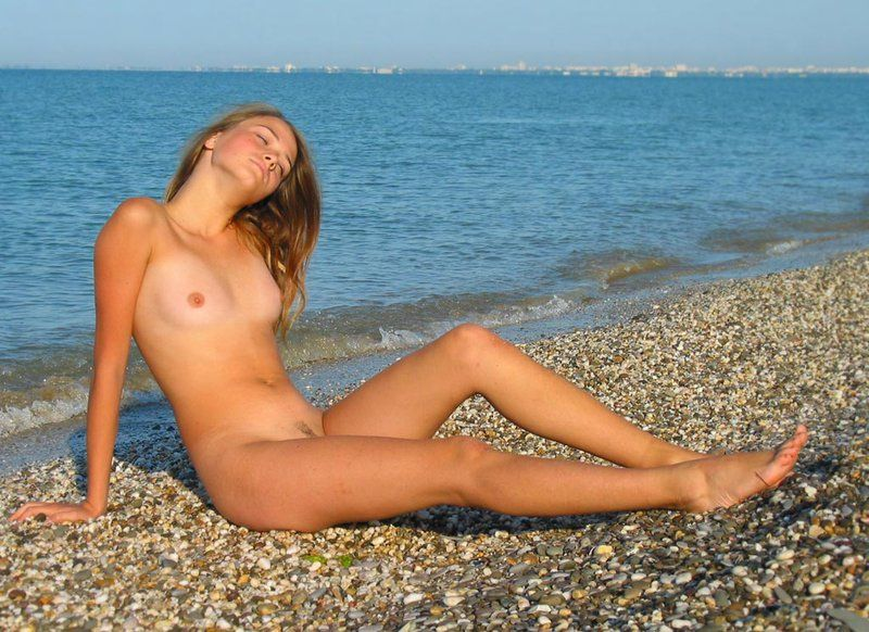 young brunette girl on the beach enjoys the sea