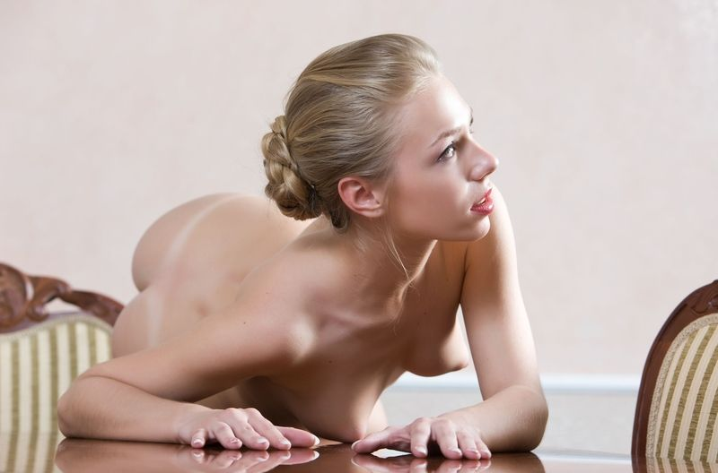 cute young blonde girl shows off her body on the table