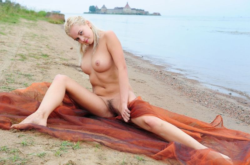 blonde girl with textile fabric at the lake with fortress