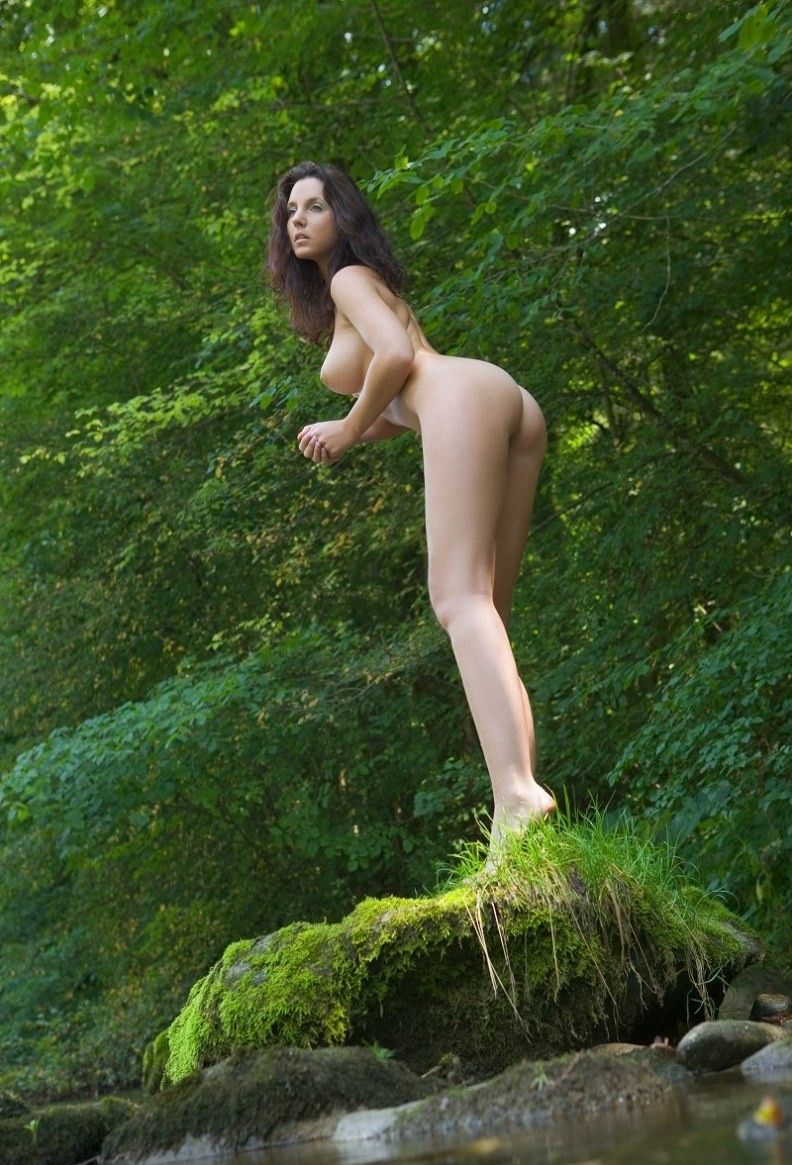 brunette girl shows off in the nature at the river