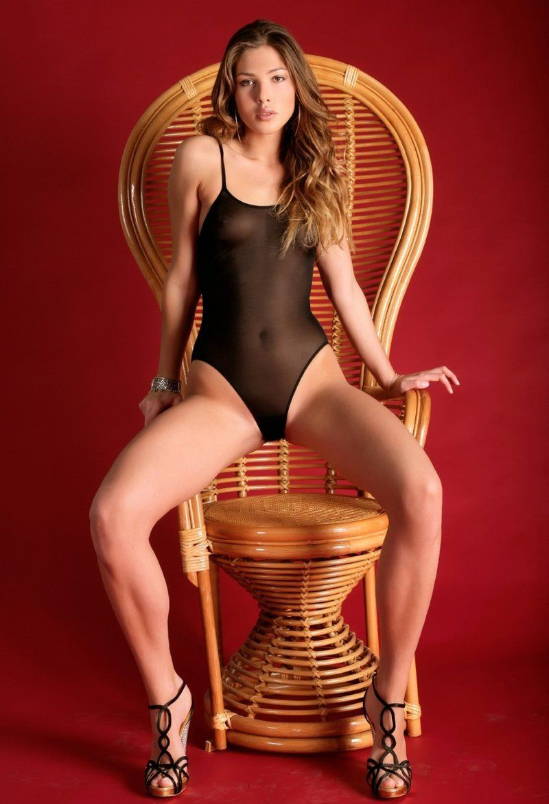 young brunette girl on the wooden chair in transparent bodysuit