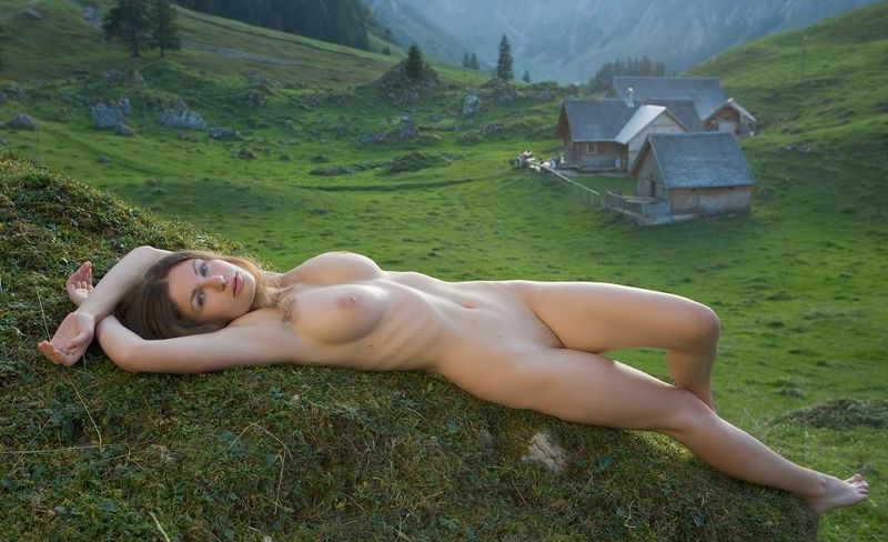 young curly brunette girl shows off in the alpine mountains above the valley tarn and a small village
