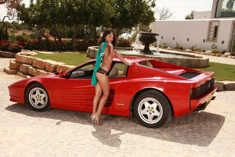 curly brunette girl strips on the ferrari testarosa