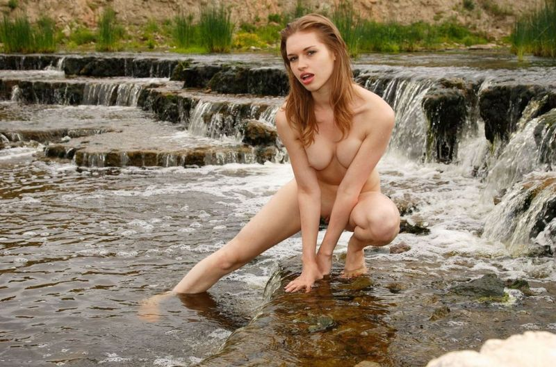 young reddish blonde girl posing at the bank of the river