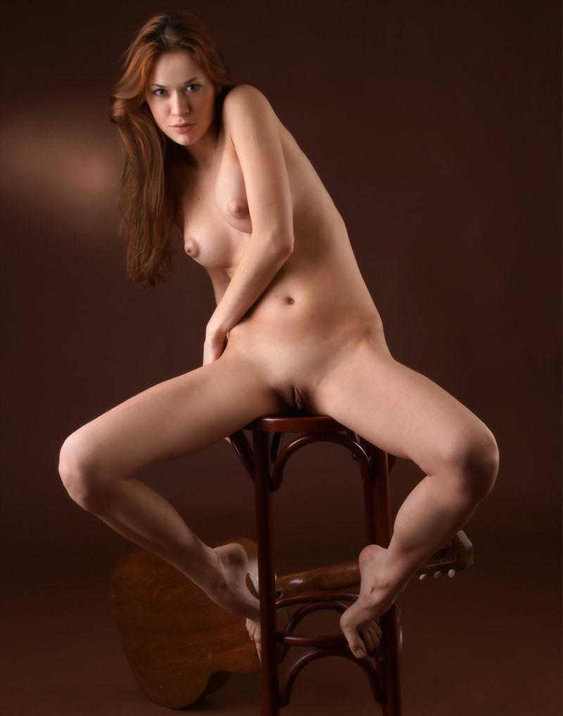 Голая девушка сидит на стуле