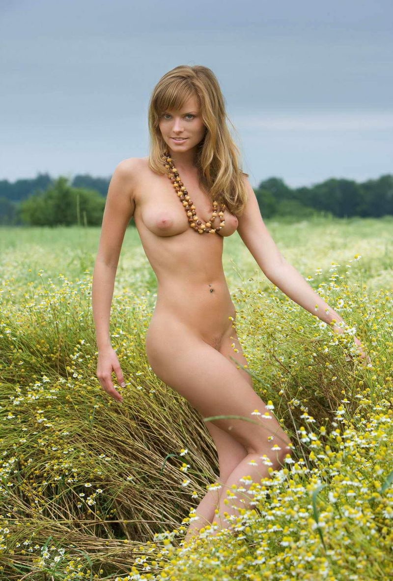 young blonde girl shows off on the field of daisy flowers