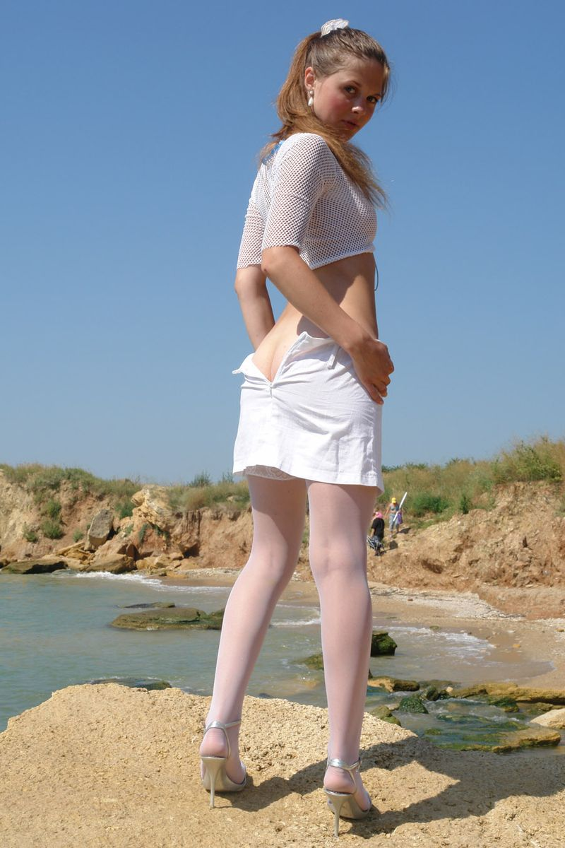 young brunette girl reveals in white top, skirt and stockings at the sea