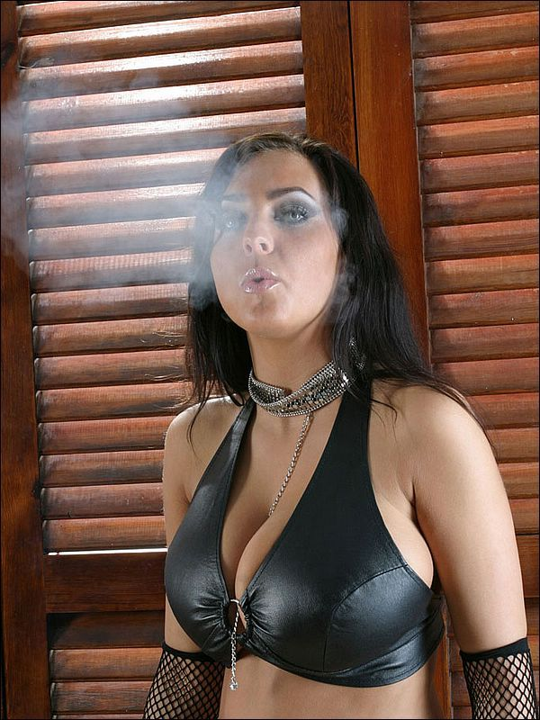 brunette girl smoking a cigarette in a latex bondage clothing