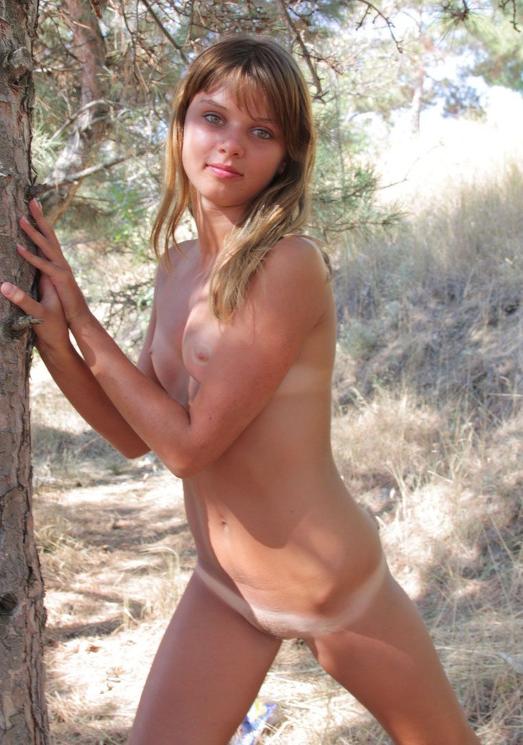cute young blonde girl with tan lines posing at the tree