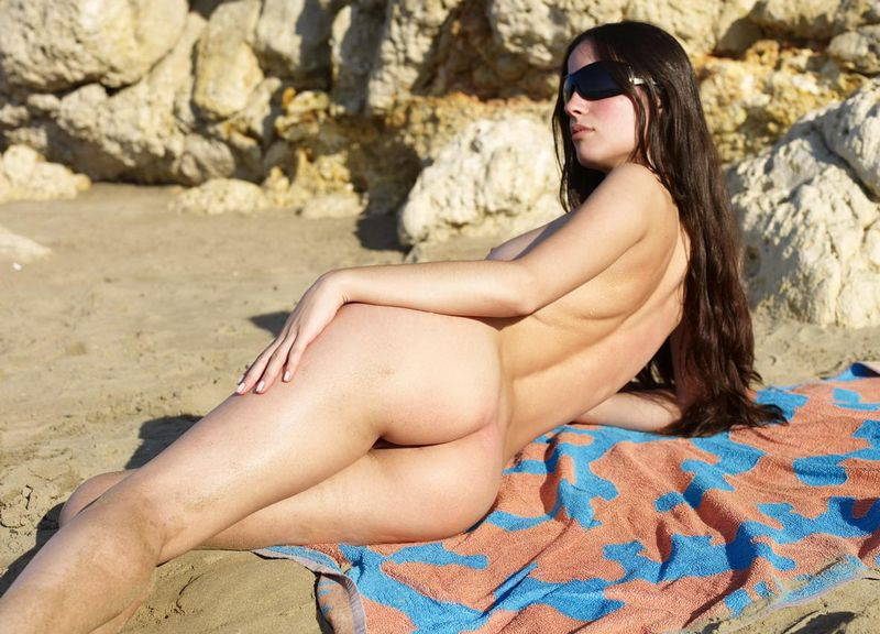 young brunette girl sunbathing with sunglasses on the beach with a towel in the sand