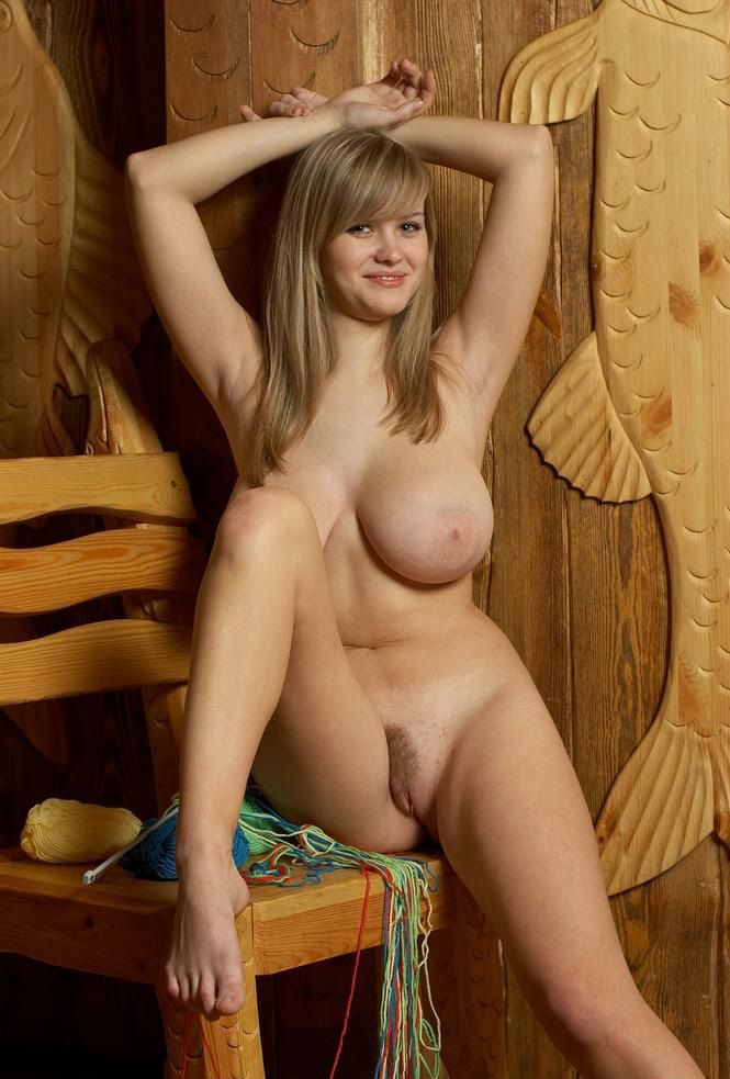 young blonde girl with big natural breasts in the wooden house with knitting yarn wool fibres