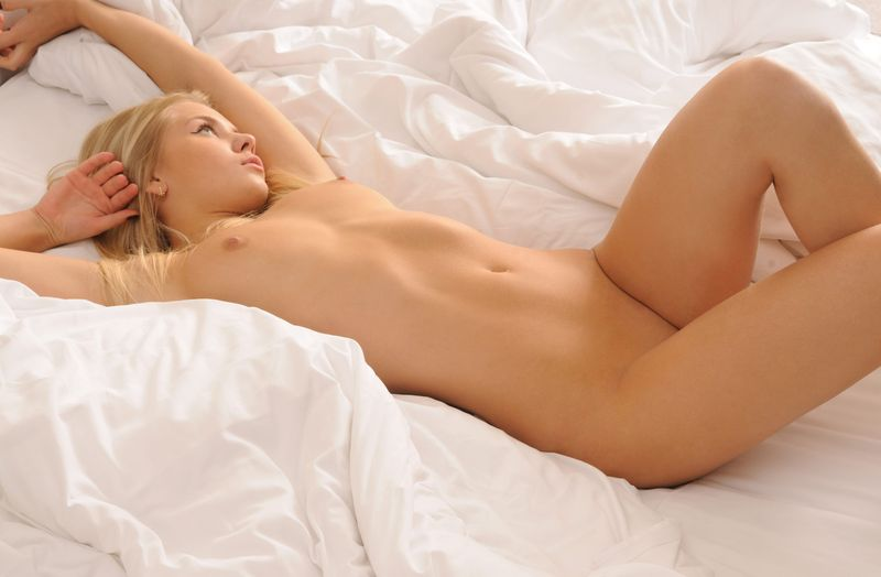 young blonde girl waking up in the bed
