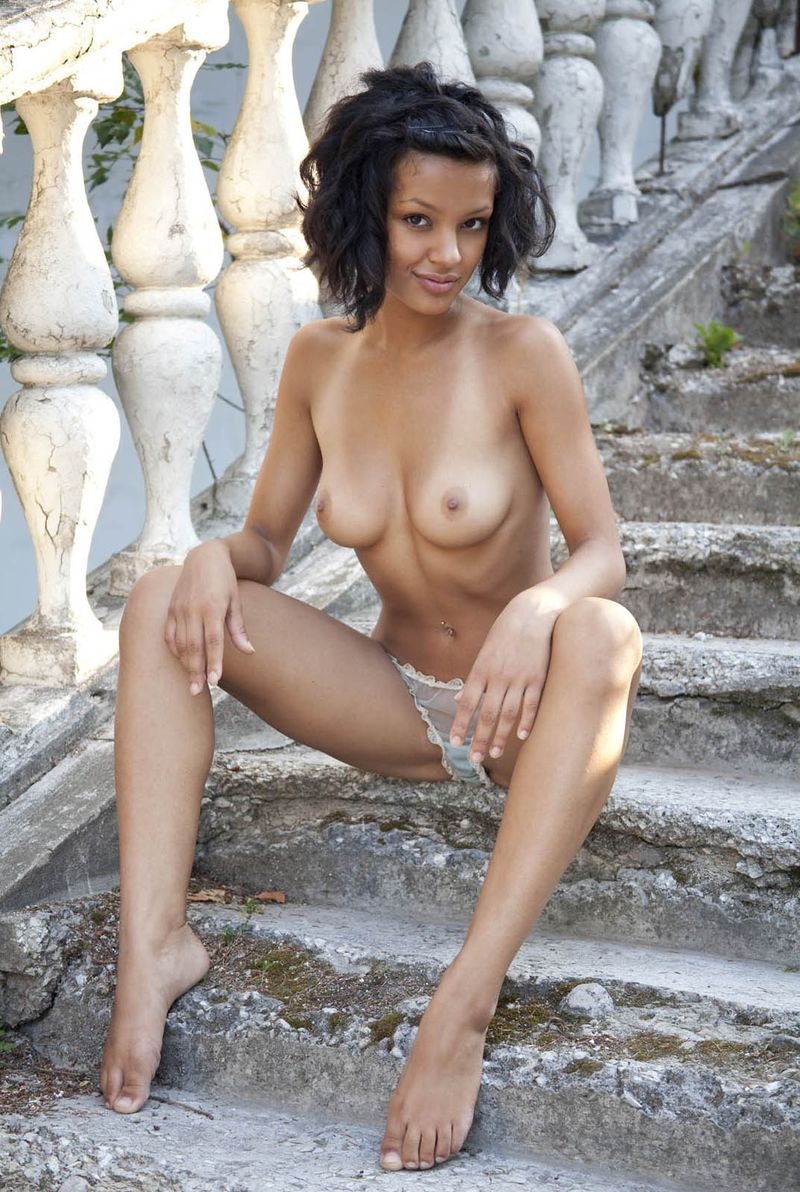 young curly black haired mulatto girl reveals on old stairs