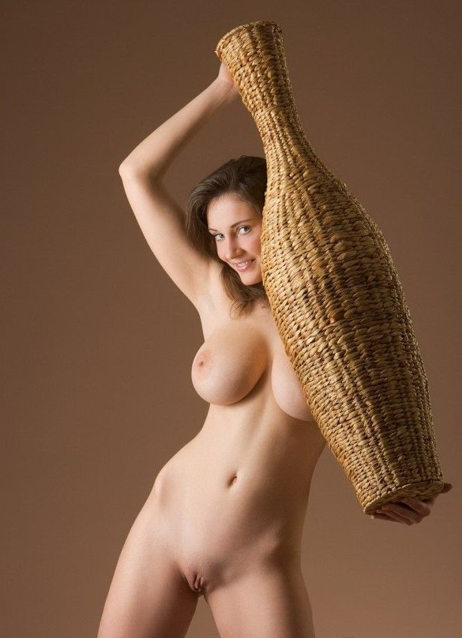 young brunette girl with full breasts posing with two rattan vases