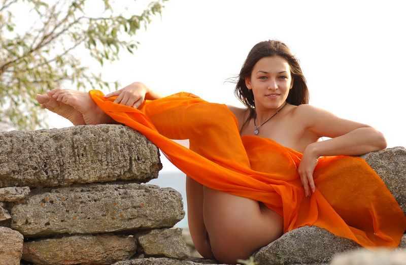 cute young brunette girl with full breasts and an orange scarf reveals near the wall of stones