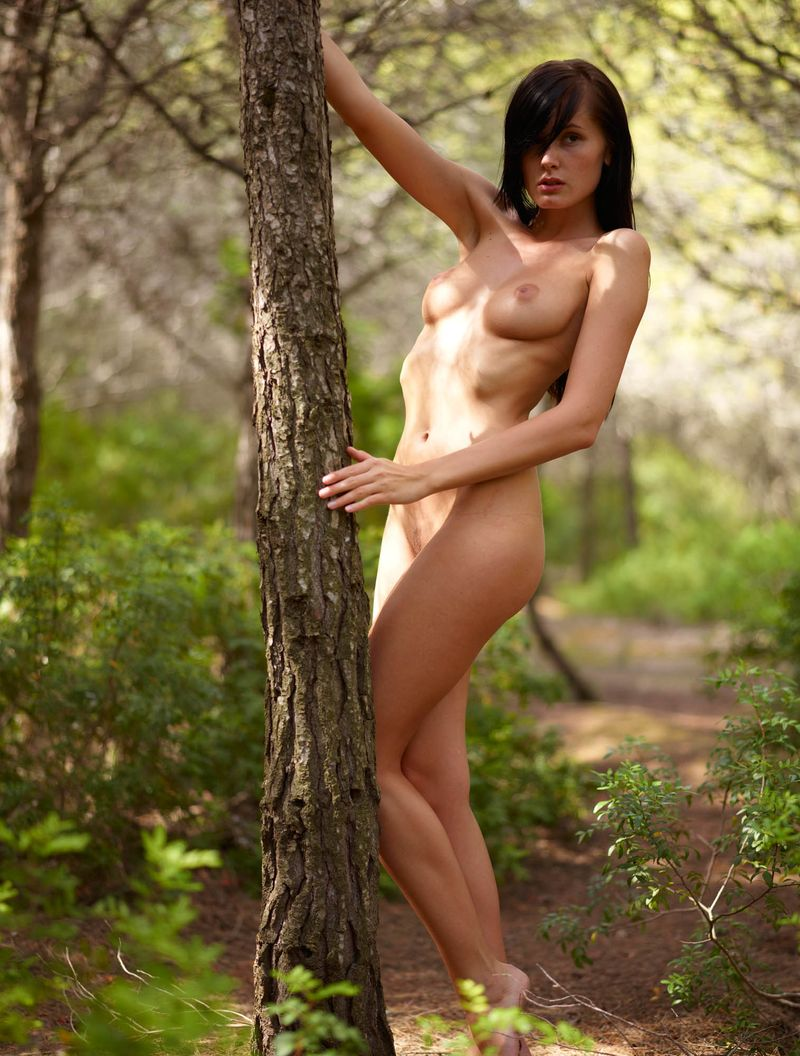 red haired girl shows off naked in the forest