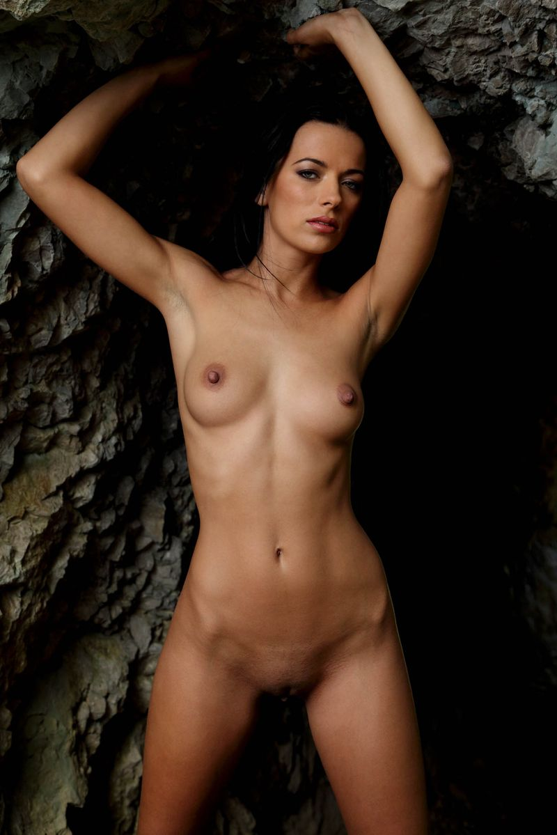 black haired girl shows off in a small cave