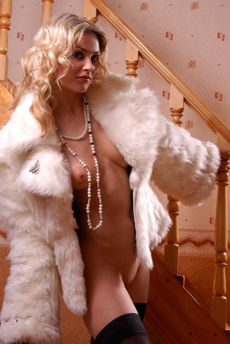 curly blonde girl wearing a fur coat and black stockings on wooden stairs