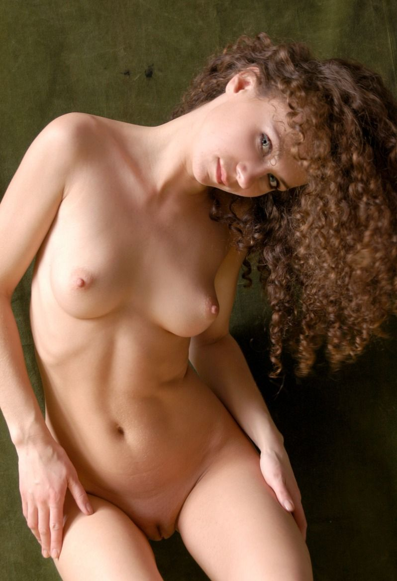 young curly brunette girl with a yellow scarf and high ankle heels undresses her gee string panties in the studio