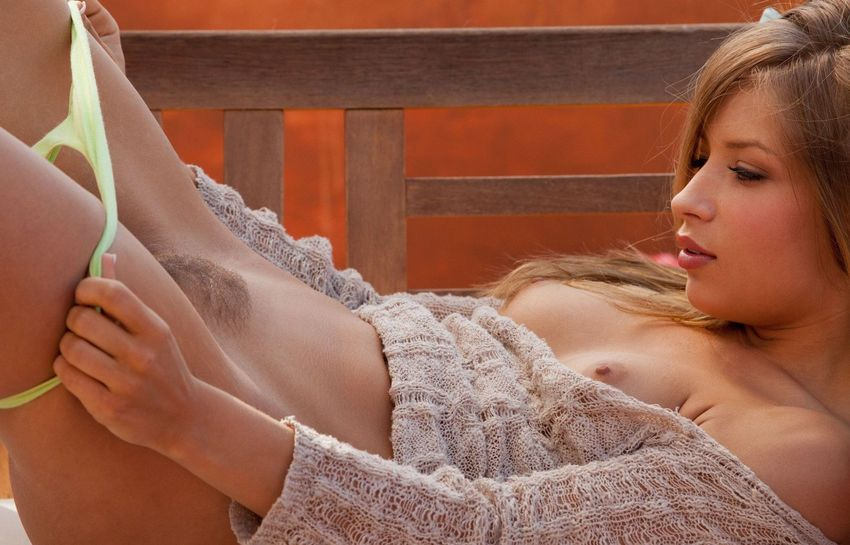 young blonde girl reveals her sweater, jean skirt and yellow panties on the wooden bench