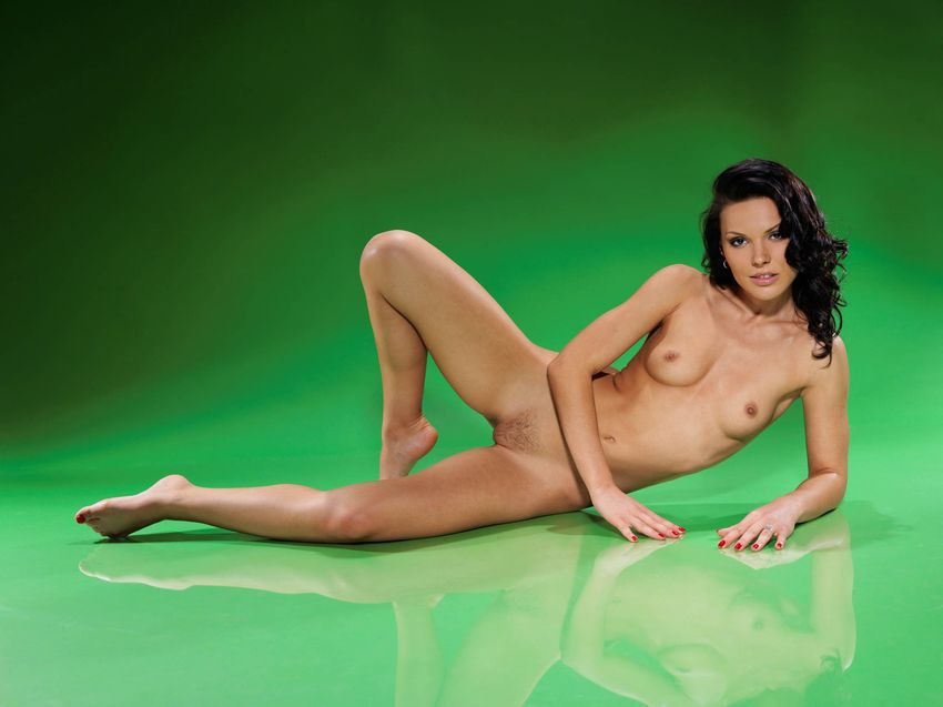 curly brunette girl shows off her body in the green studio