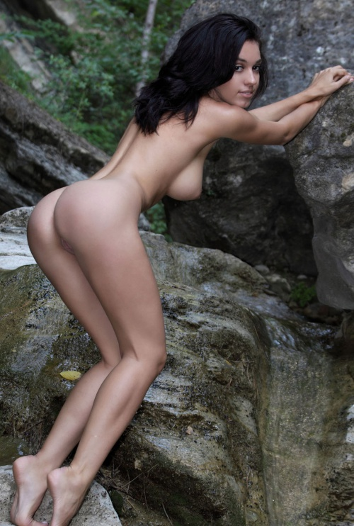 young black haired girl undresses her white top in the nature on rocks near small cascade waterfalls