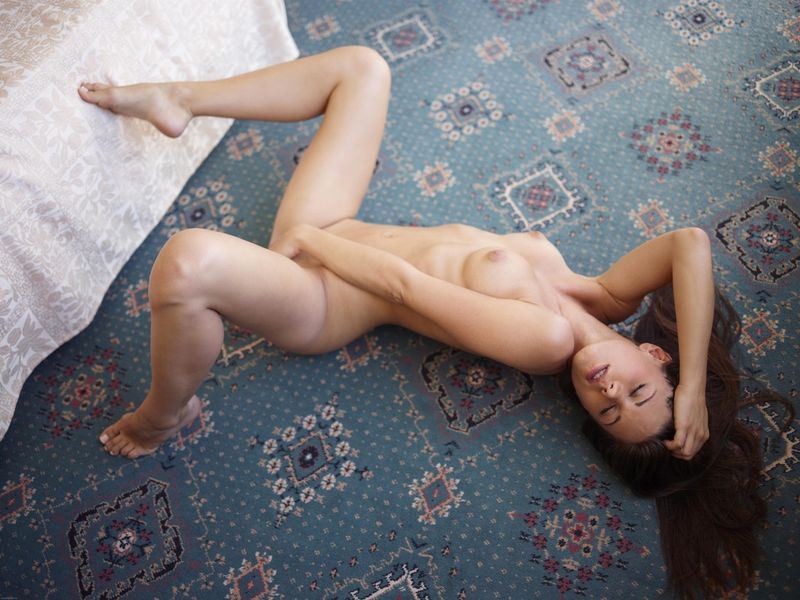 young brunette girl shows off on the carpet in the bedroom at home