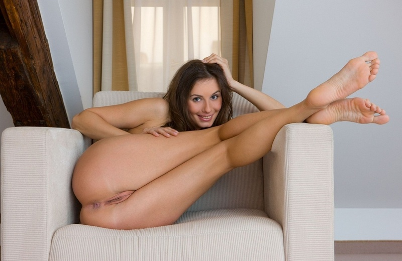 young brunette girl with blue eyes shows off on the sofa chair at home
