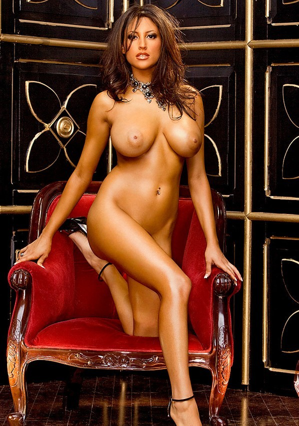 brunette girl with with big breasts wearing a necklace, navel piercing, black belt and high heels on the red antique sofa chair