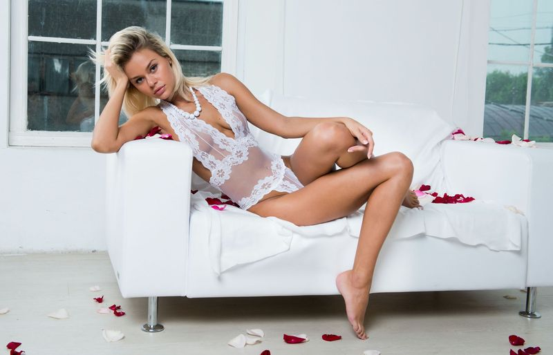 young blonde girl undresses her white camiknicker teddy lingerie on the couch with a red rose and petals leaves