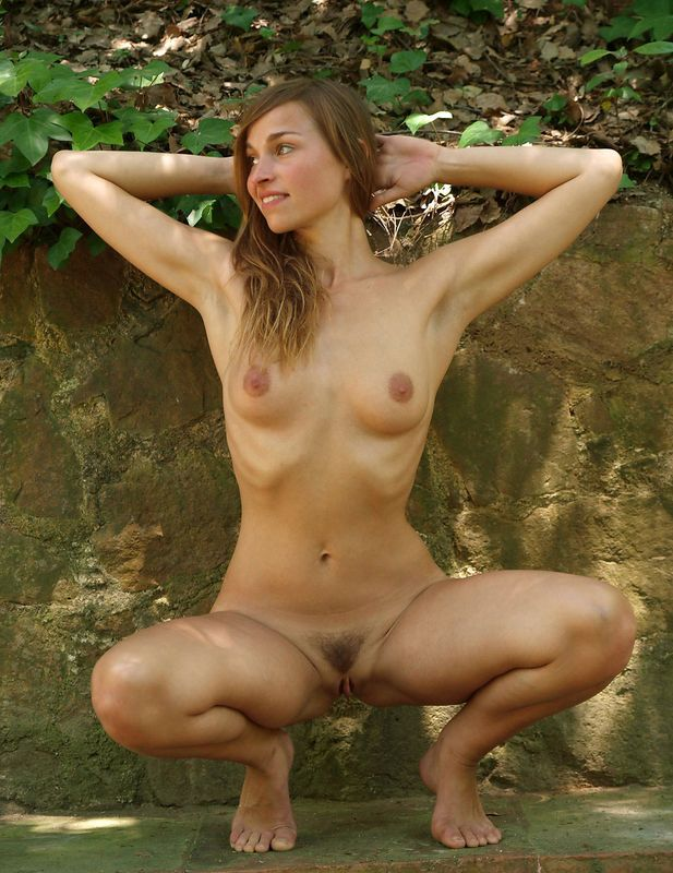 young brunette girl naturist posing nude on the walking trail in the public park with small cascade waterfalls