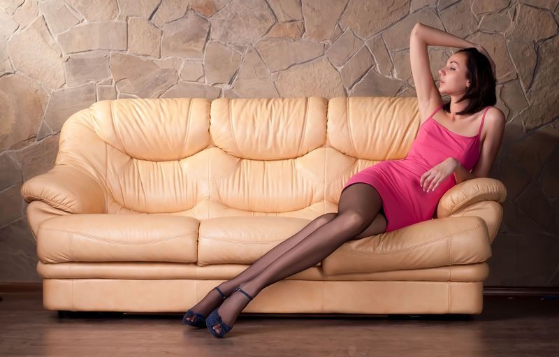 young brunette girl with a nipple piercing reveals her pink dress and black hold-ups with garter belts suspenders on the leather sofa at home