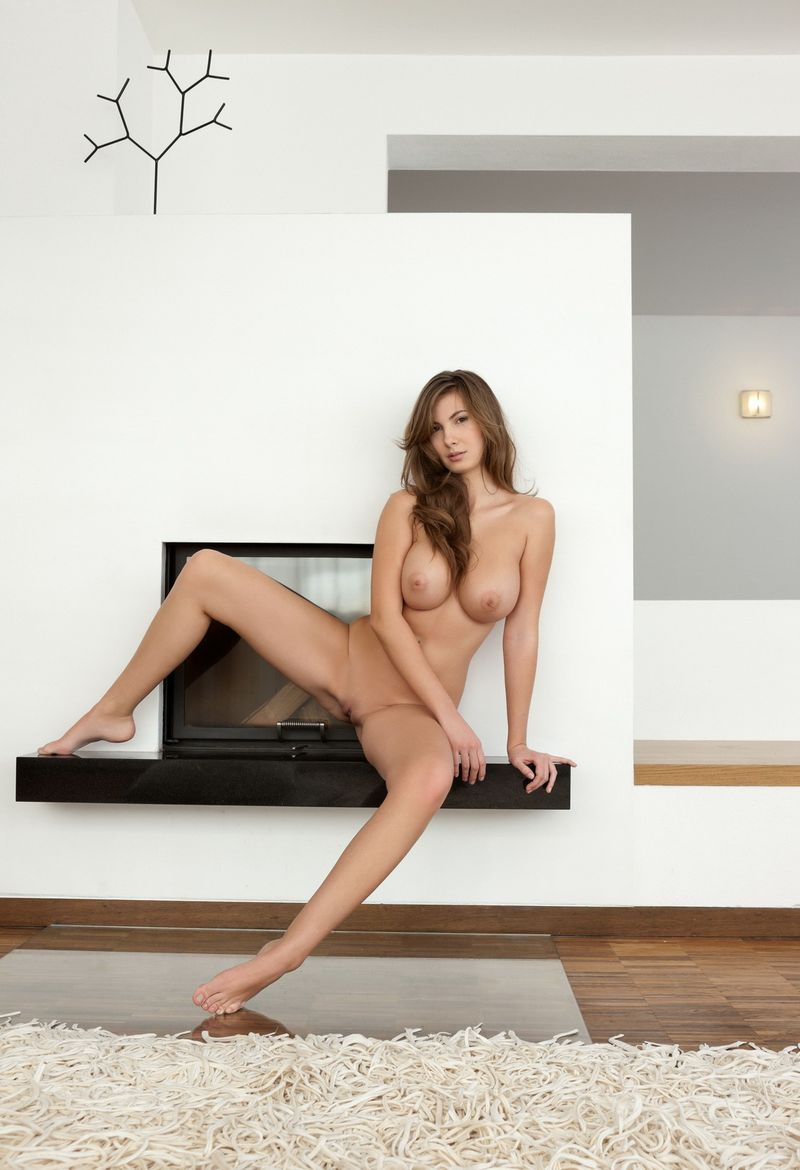 young curly brunette girl with a navel piercing and full breasts posing in front of the fireplace at home